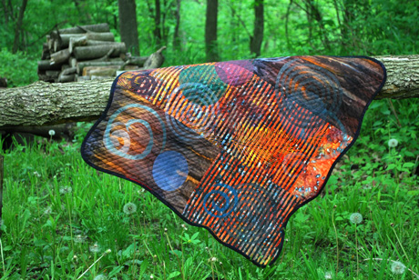 quilt on a wood pile